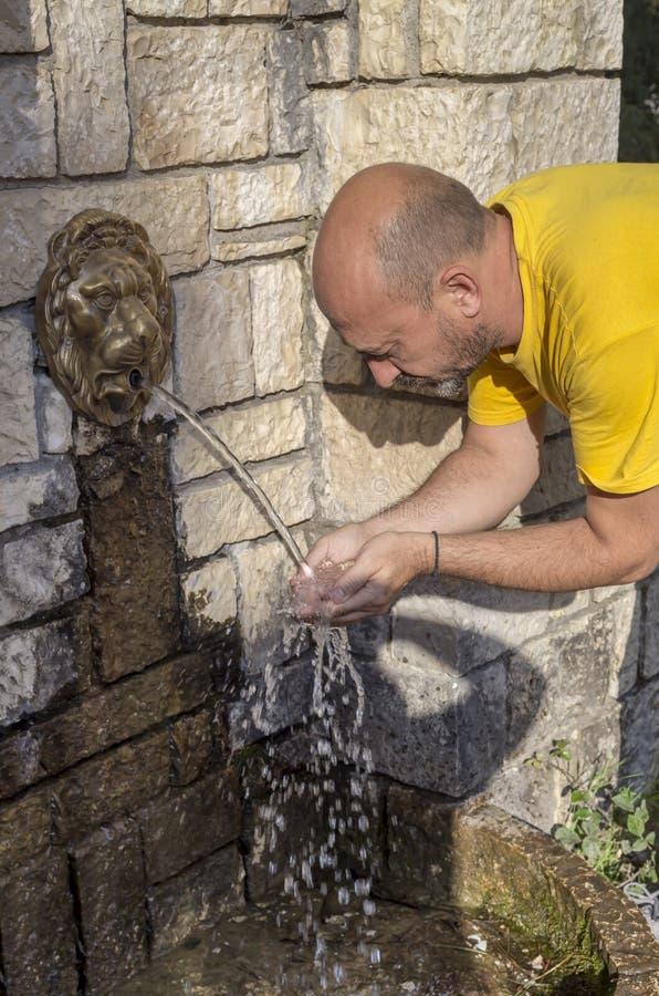 Een mens giet in zijn handenwater uit een bergbron aan drank royalty-vrije stock foto