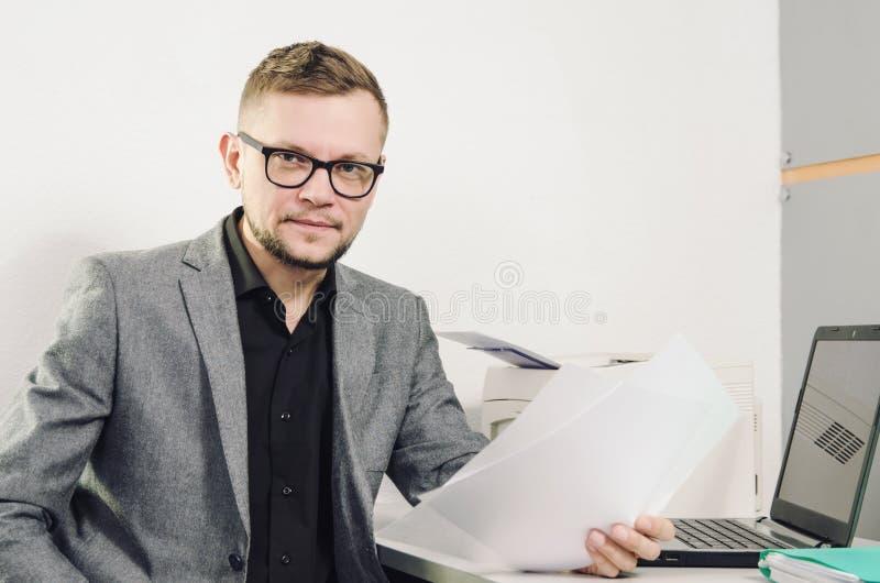 Een mens in glazen en een jasje met de documenten stock fotografie
