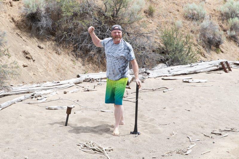 Een mens heft zijn vuist in de lucht na het drijven van een metaalstaak in het zandige strand met een sleehamer op stock fotografie