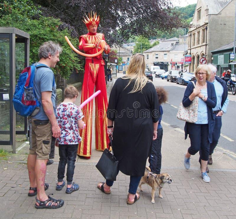 Een mens in een helder kostuum op stelten die ballondieren voor een familie in de straat maken bij hebden festival van brug het o royalty-vrije stock foto's