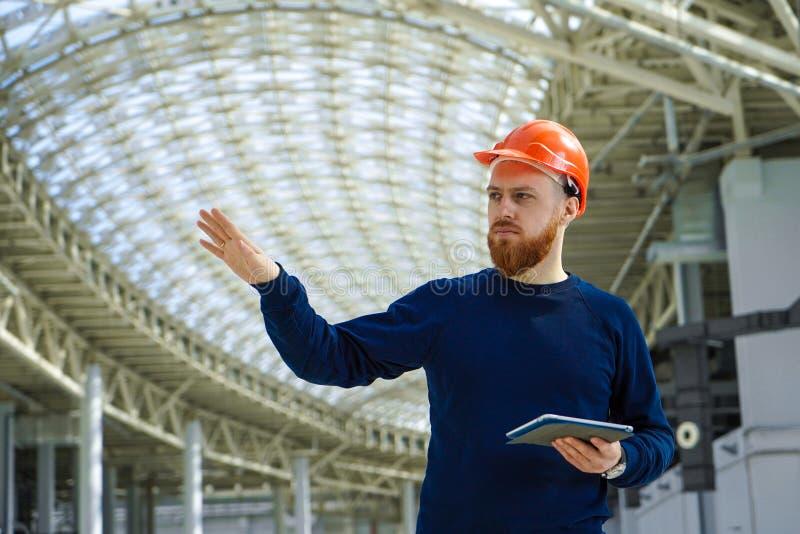 Een mens in een helm in een grote ruimte met een tablet stock foto's