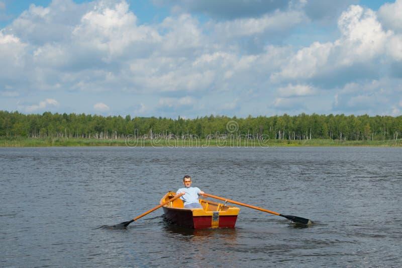 Een mens, in het centrum van het meer, zwemt in een boot met roeispanen, tegen de achtergrond van een mooi landschap stock foto's