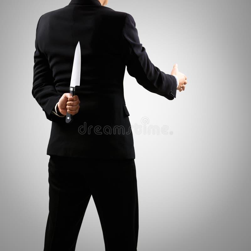Een mens in het mes van de kostuumholding achter rug stock foto