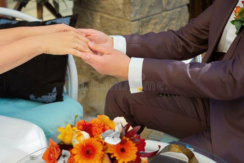 Een mens houdt de handen van zijn bruid stock fotografie