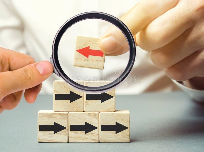 Een mens houdt een houten blok met rode pijl die de tegenovergestelde richtings zwarte pijlen onder ogen zien individueel advies  royalty-vrije stock foto
