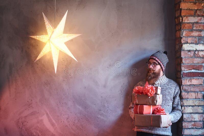 Een mens houdt Kerstmisgiften stock afbeeldingen