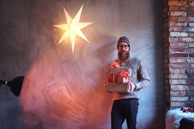 Een mens houdt Kerstmisgiften stock fotografie