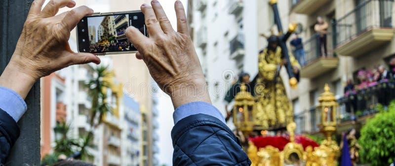 Een mens houdt op zijn mobiele telefoon het beeld van de stap van de Optocht van Jesus Nazarene in Huelva, Spanje royalty-vrije stock afbeelding