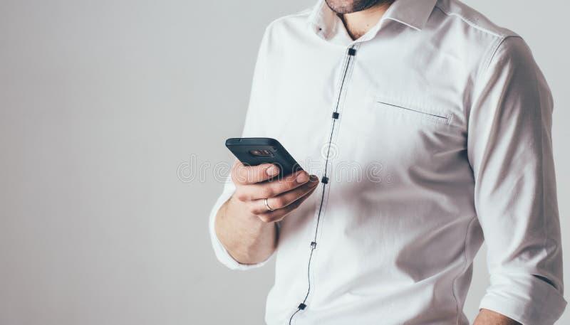 Een mens houdt een telefoon in zijn hand op de witte achtergrond Hij is gekleed in een wit overhemd met zwarte tussenvoegsels en  stock afbeelding