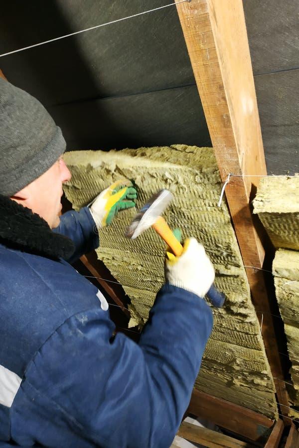 Een mens installeert een thermische isolatielaag van een thermisch dak - gebruikend panelen die van steenwol, het opzetten tussen royalty-vrije stock afbeeldingen