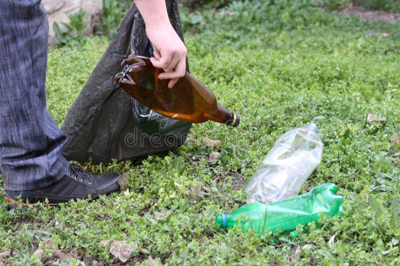 Een mens in jeans is bezig geweest met de ecologie van aard en verzamelt plastic flessen in een plastic zak die de grond schoonma stock fotografie