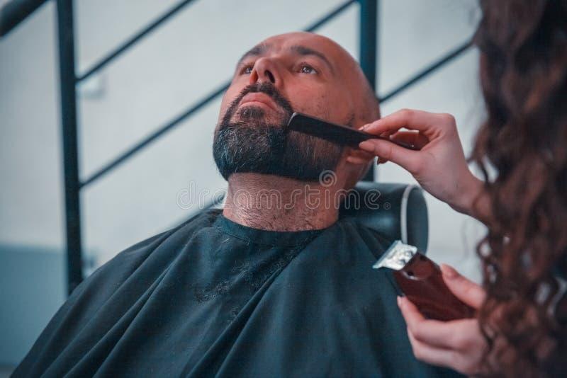 Een mens in een kapperswinkel voor een professionele behandelingshaar en een baard stock fotografie