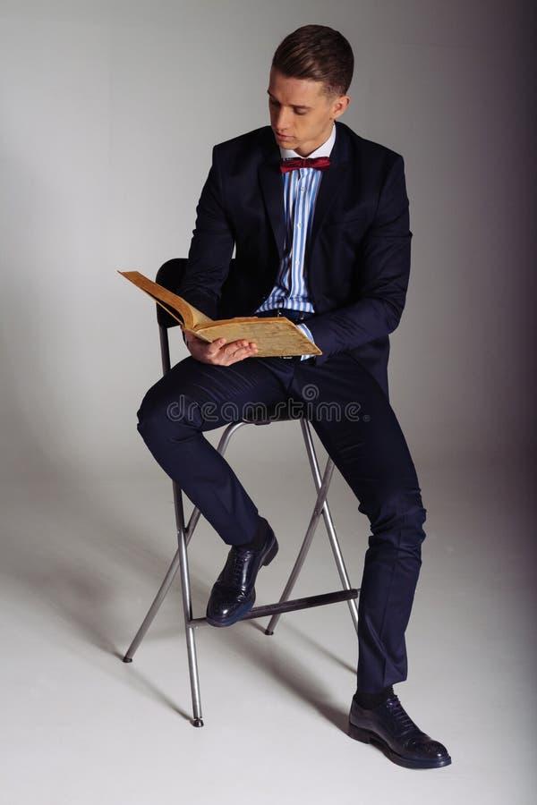 Een mens, een kerel in een blauw kostuum, zit op een stoel en leest een oud boek, het concept kennis, studie, wetenschap, zaken,  royalty-vrije stock foto's