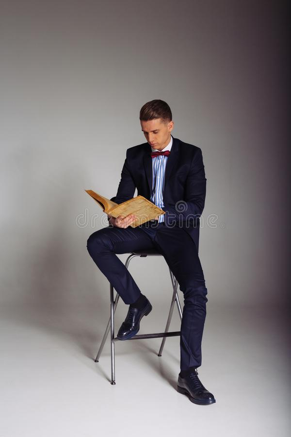 Een mens, een kerel in een blauw kostuum, zit op een stoel en leest een oud boek, het concept kennis, studie, wetenschap, zaken,  royalty-vrije stock foto
