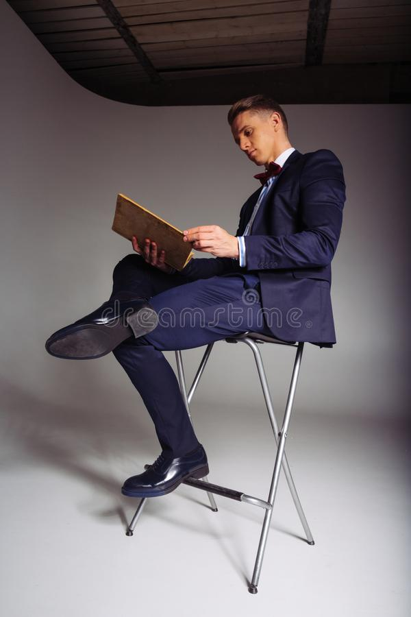 Een mens, een kerel in een blauw kostuum, zit op een stoel en leest een oud boek, het concept kennis, studie, wetenschap, zaken,  stock foto