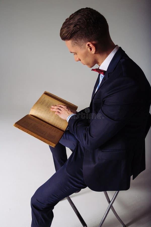 Een mens, een kerel in een blauw kostuum, zit op een stoel en leest een oud boek, het concept kennis, studie, wetenschap, zaken,  stock foto's