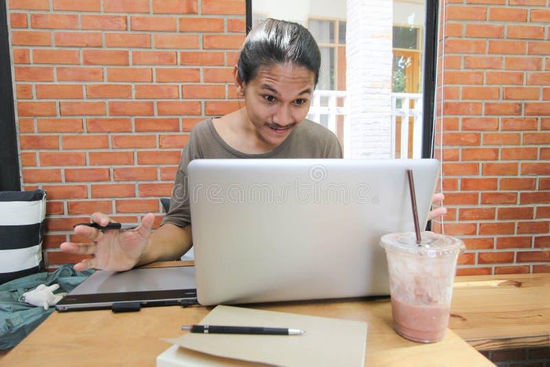 Een mens kijkt aan laptop verraste computer, Geschokte Aziatische mens met h stock foto's