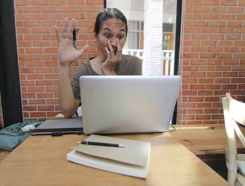 Een mens kijkt aan laptop verraste computer, Geschokte Aziatische mens met h royalty-vrije stock afbeelding