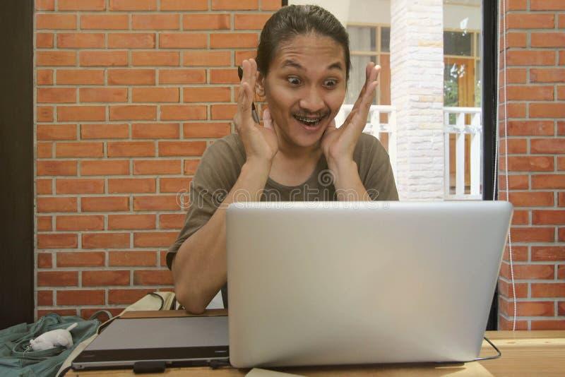 Een mens kijkt aan laptop verraste computer, Geschokte Aziatische mens met h royalty-vrije stock afbeeldingen