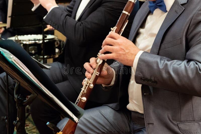 Een mens in een kostuum speelt de klarinet Fanfarekorps Muzikaal thema De mannelijke vingers duwen op de sleutels op de pijp Clos stock afbeeldingen