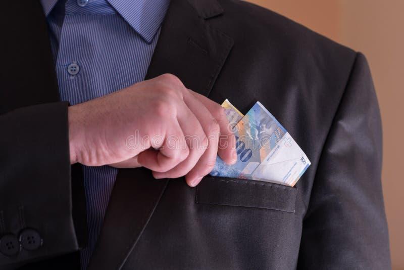 Een mens in een kostuum trekt zich van zijn zak Zwitserse bankbiljetten terug royalty-vrije stock afbeeldingen