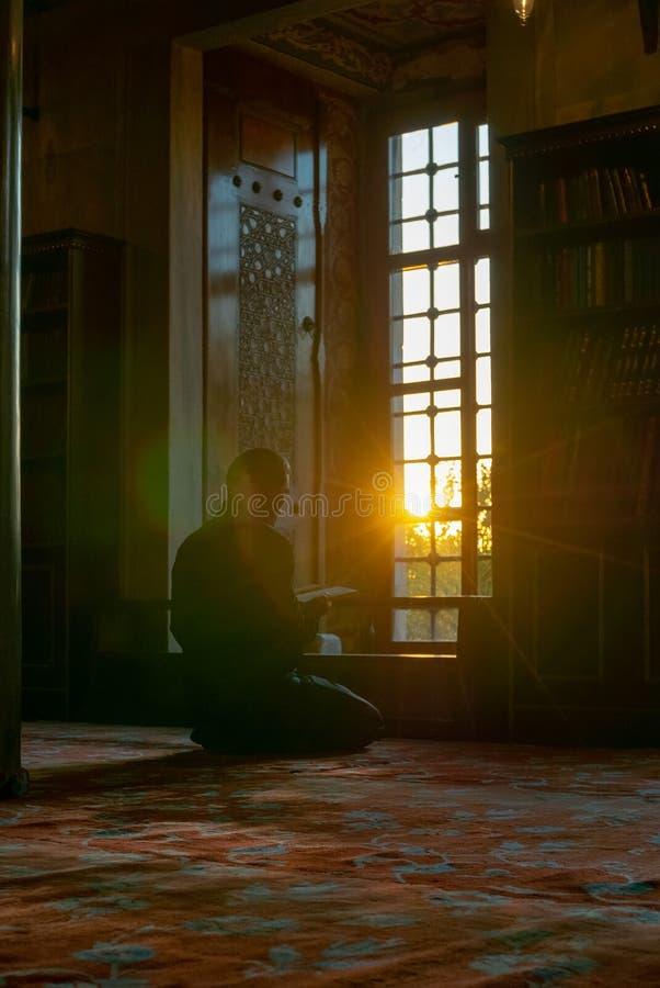 Een mens leest Koran of Al Quran met opzettelijke de zonvestiging van de lensgloed binnen Sultanahmet-moskee in Istanboel, Turkij stock afbeeldingen