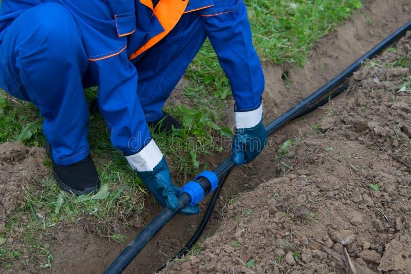 Een mens legt in de opgegraven geul, een waterpijpleiding en een elektrische kabel stock fotografie