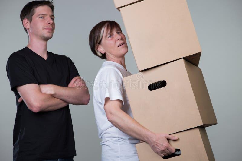 Een mens let enkel op terwijl een vrouw zware cardboxes draagt royalty-vrije stock afbeelding