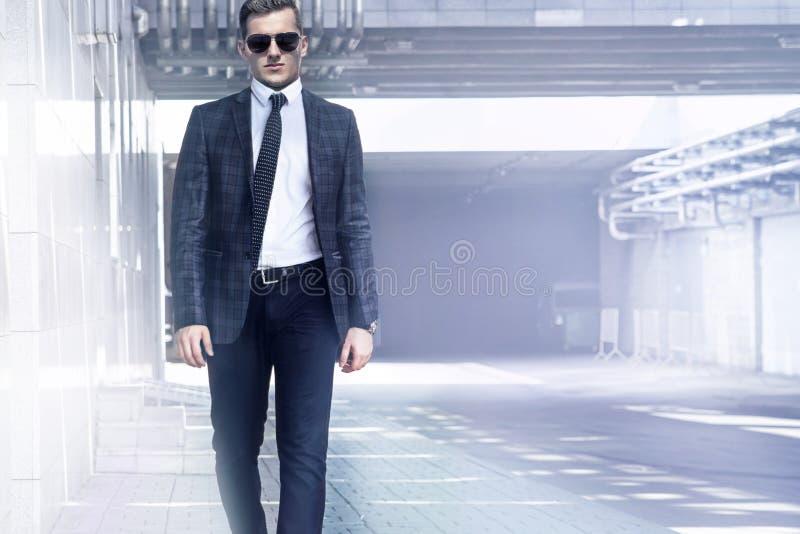 Een mens loopt in een kostuum op de achtergrond van de moderne stad stock afbeeldingen