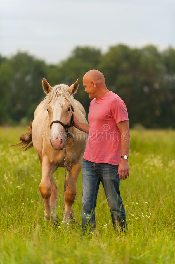 Een mens loopt met zijn paard royalty-vrije stock fotografie
