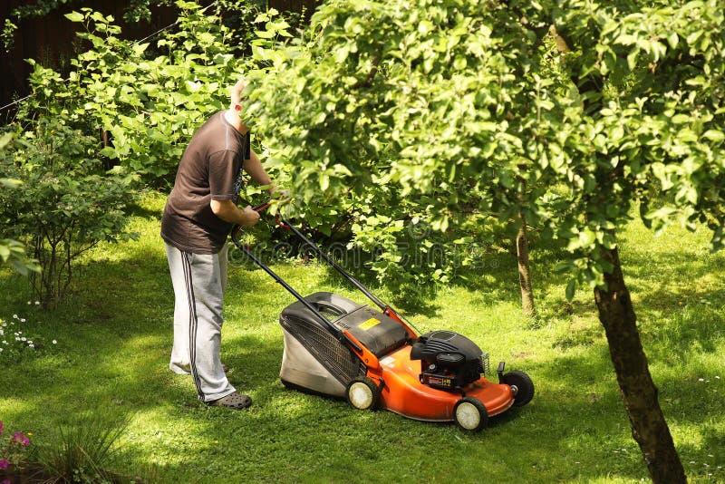 Een mens maait het gras met een grasmaaier op het gazon van zijn tuin Zorg voor Engels gazon Het buitenhuis van het landschapsont royalty-vrije stock foto