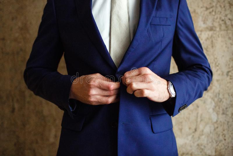 Een mens maakt knopen matroos op zijn hand vast zijn horloge stock afbeeldingen