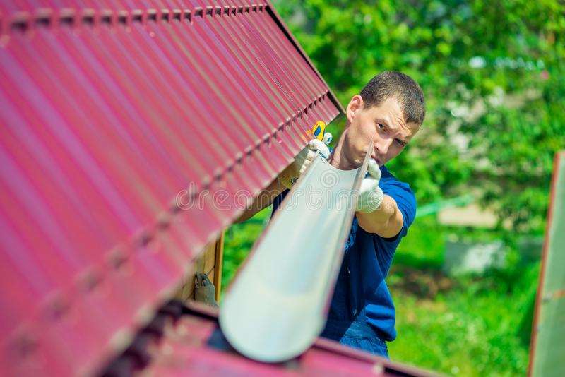 Een mens maakt een pijp aan afvoerkanaalregenwater van het dak stock afbeeldingen