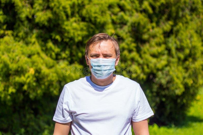 Een mens in een masker van allergie, in een witte T-shirt, bevindt zich in het park royalty-vrije stock foto