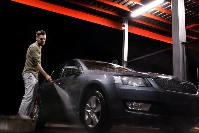 Een mens met een baard of autowasmachine wast een grijze auto met een hoge drukapparaat bij nacht in een autowasserette stock afbeelding