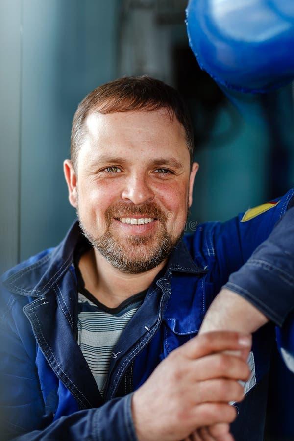 Een mens met een baard in werkkledij glimlacht een sneeuwwitte glimlach bij de werkplaats in het ketelruim Portret van gelukkig royalty-vrije stock foto