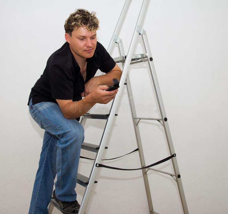 Een mens met een cel op een trapladder op een witte achtergrond stock afbeeldingen