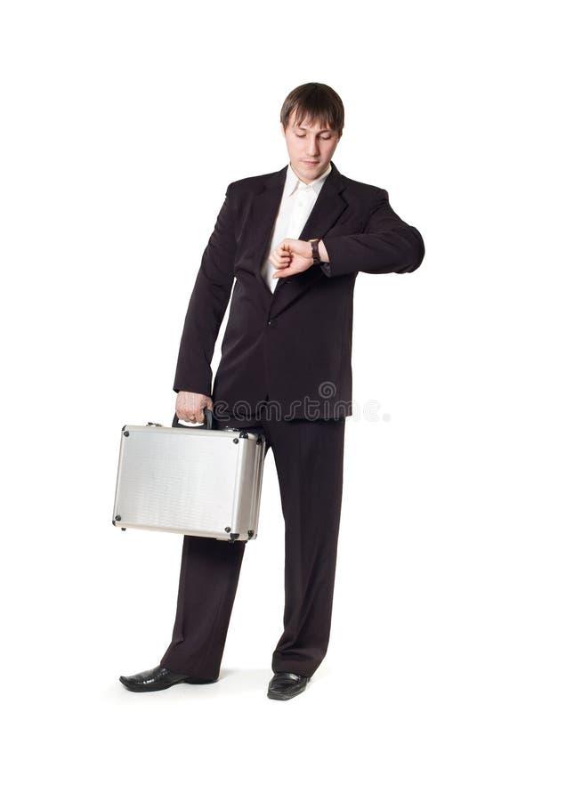 Een mens met een aktentas die zijn horloge bekijkt stock afbeeldingen