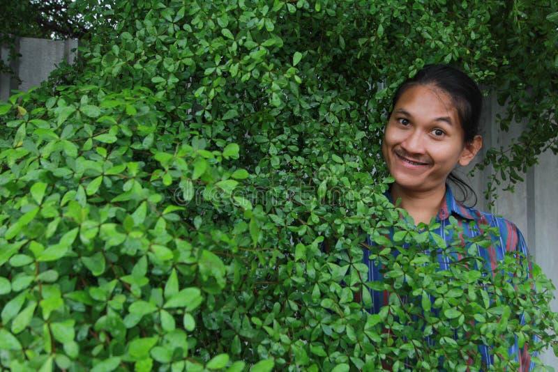 Een mens met een Lang haar en een snor die uit van bushe gluren stock afbeeldingen