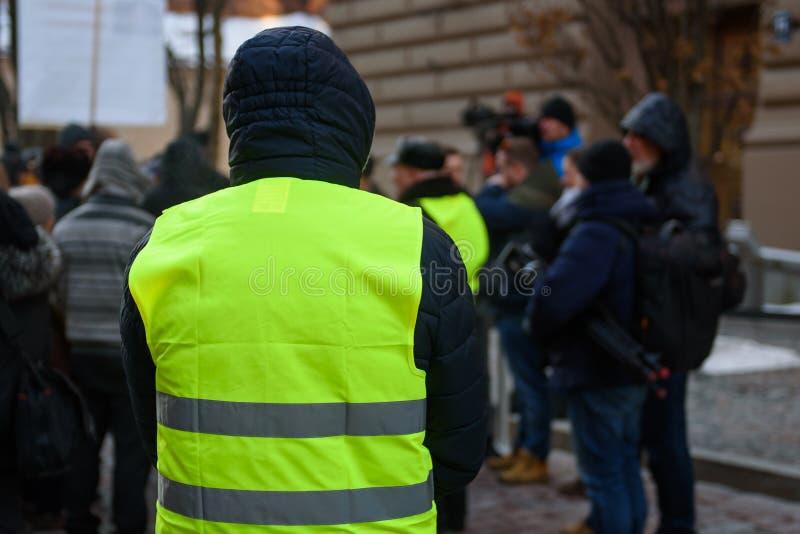 Een mens, met geel vest, tijdens Demonstratie tegen nieuwe coalitie van regering van Letland stock foto