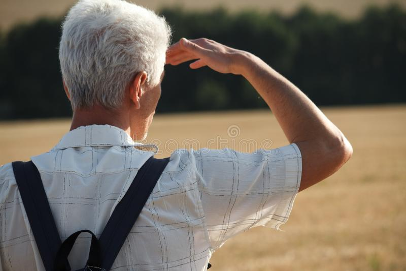 Een mens met grijs haar en een zwarte rugzak achter zijn rug bevindt zich op het stoppelveld van een tarwegebied, hief zijn hand  royalty-vrije stock foto's