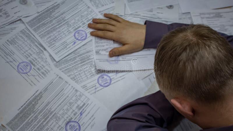 Een mens met handelspapieren en contracten Crisissituatie Problemen met banken, schulden op betalingen, overdrachten en leningen stock afbeelding