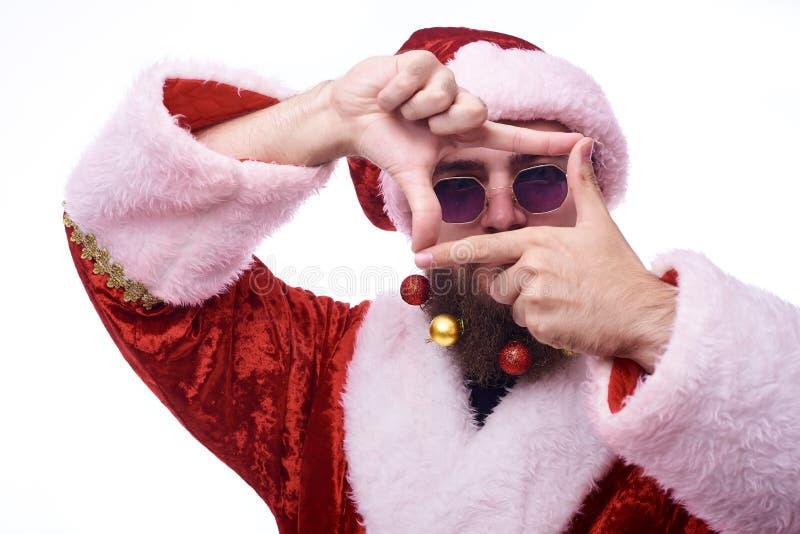 Een mens met Kerstmisspeelgoed in een baard en in een kostuum van Santa Claus houdt indient voorzijde van zijn gezicht in de vorm royalty-vrije stock foto