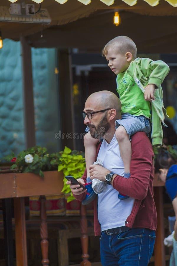 Een mens met een kind die op zijn schouders onderaan de straat lopen royalty-vrije stock fotografie