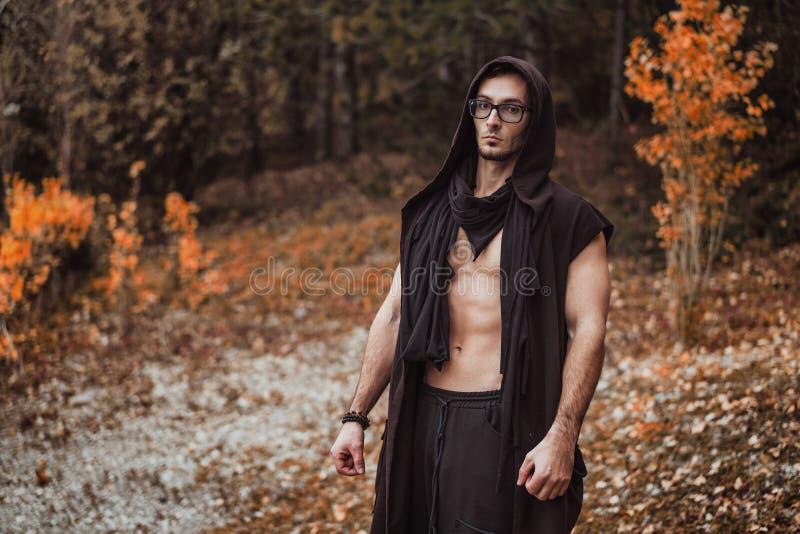 Een mens met een naakt torso bevindt zich op de achtergrond van het de herfstbos stock afbeeldingen