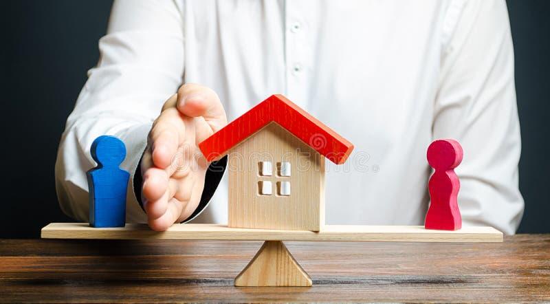 Een mens met een palm scheidt het huis van de echtgenoot ten gunste van de vrouw Bezitsscheiding, onroerende goederenafdeling daa stock afbeeldingen