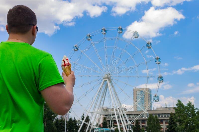 Een mens met een roomijs in zijn hand bevindt zich in een pretpark bekijkend een ferriswiel stock afbeelding