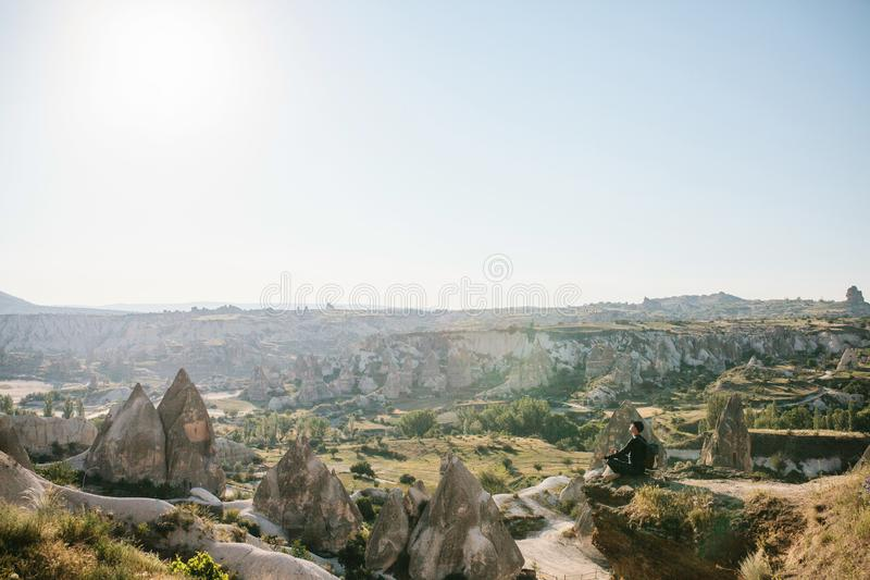 Een mens met een rugzak zit bovenop een heuvel in Cappadocia in Turkije royalty-vrije stock foto