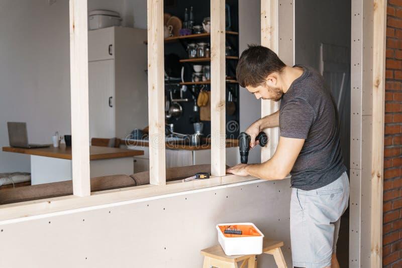 Een mens met een schroevedraaier in zijn hand bevestigt een houten kader voor een venster in zijn huis royalty-vrije stock foto