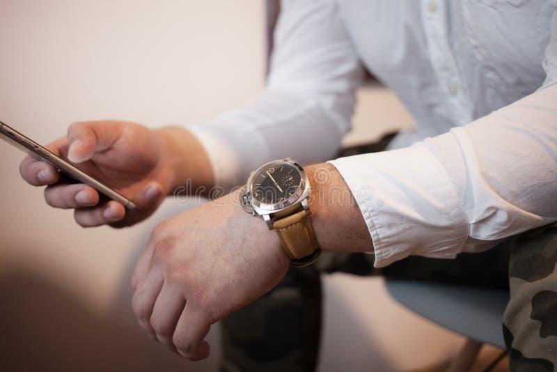 Een mens met smartphone in ontspannen stelt in een wit overhemd typt sms psychologie en onderhandelingsconcept stock fotografie